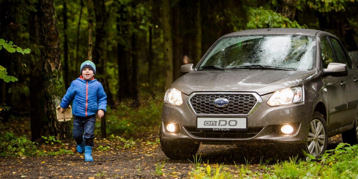 Ребёнок и автомобиль Datsun в осеннем лесу.