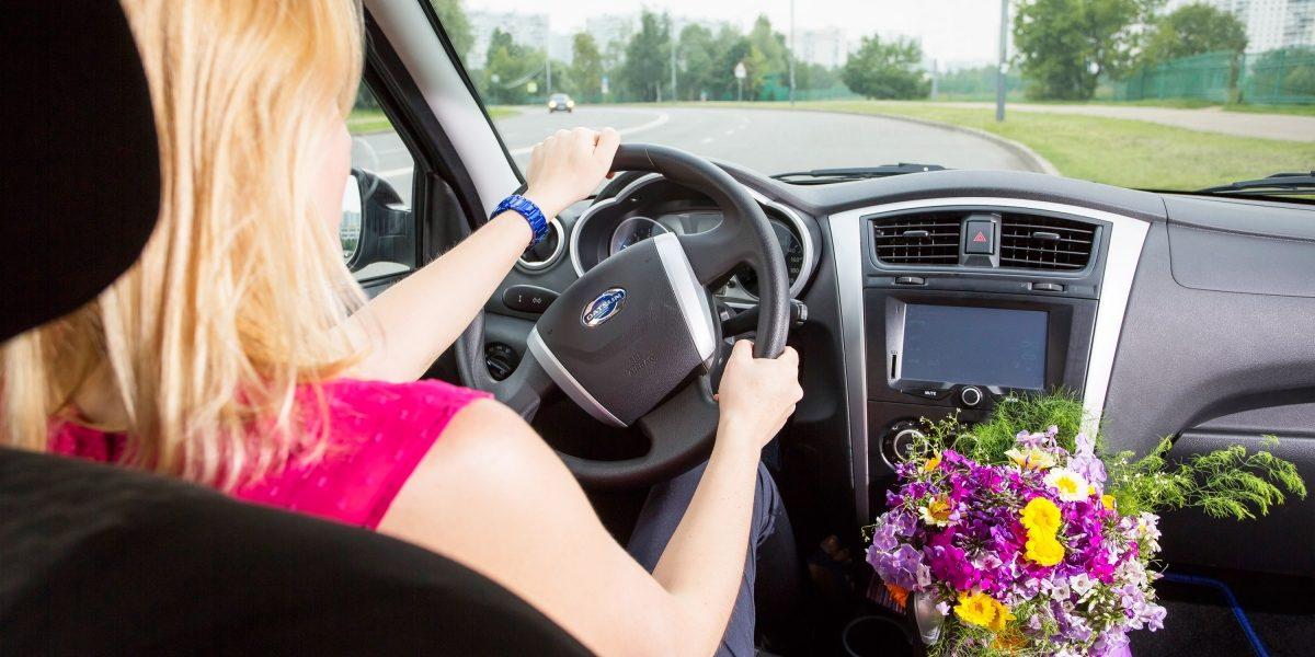Женщина за рулем автомобиля Datsun.