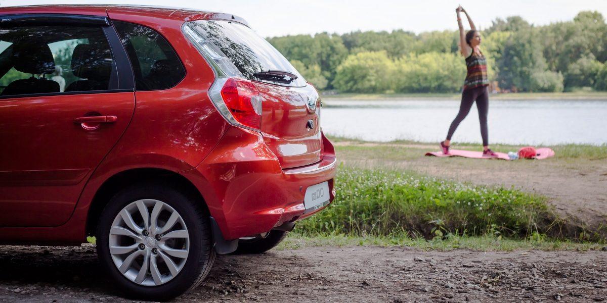 Девушка занимается спортом рядом с автомобилем Datsun.