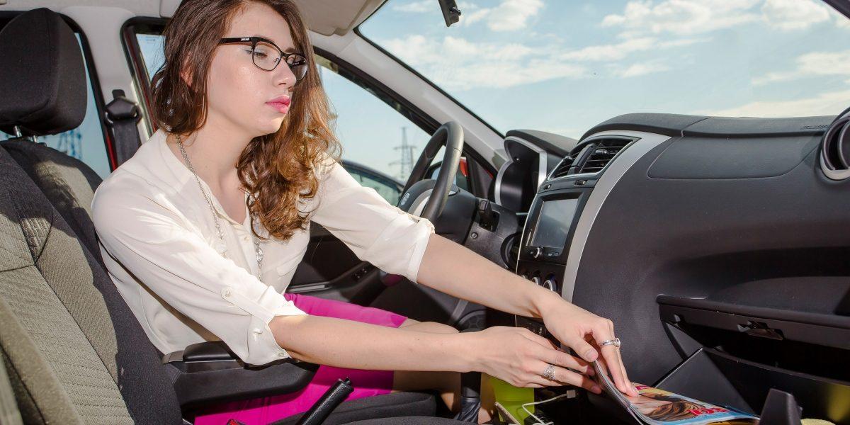 Девушка открывает бардачок автомобиля Datsun.