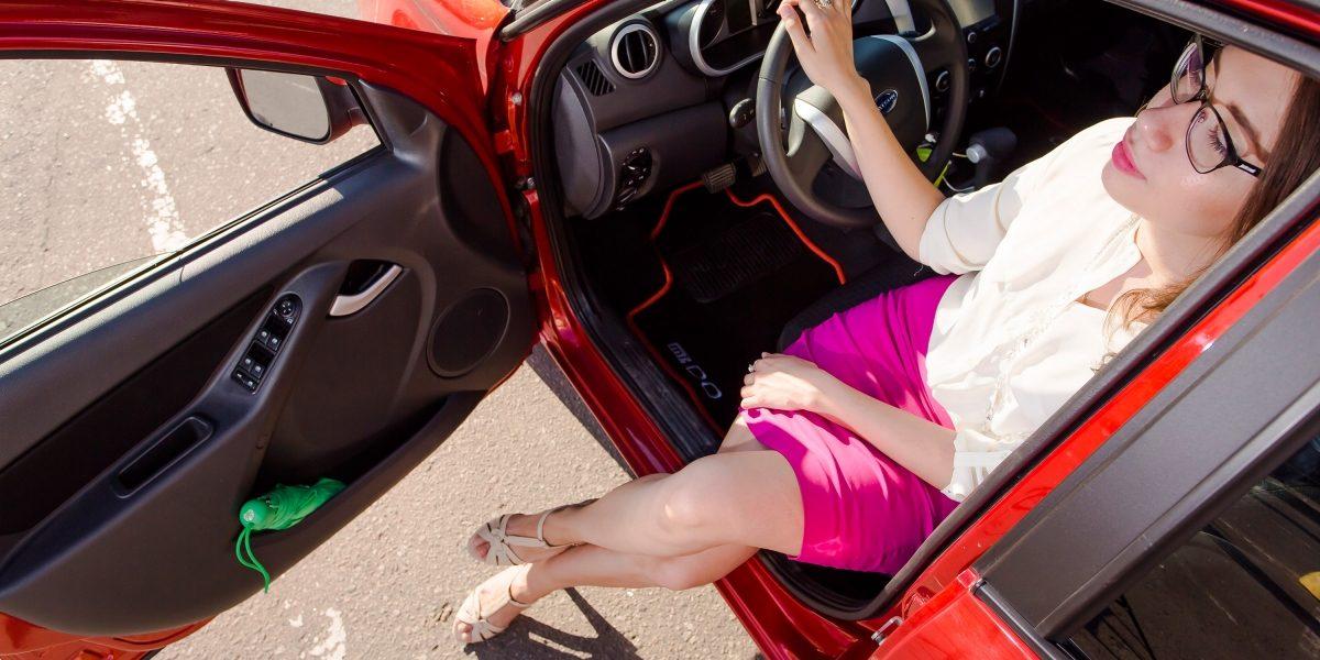 Девушка сидит на переднем сидении автомобиля Datsun.