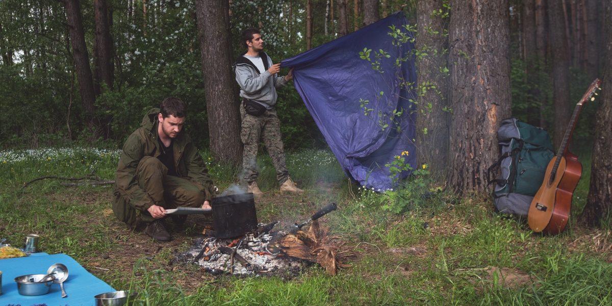 Друзья раскидывают походный лагерь в лесу.