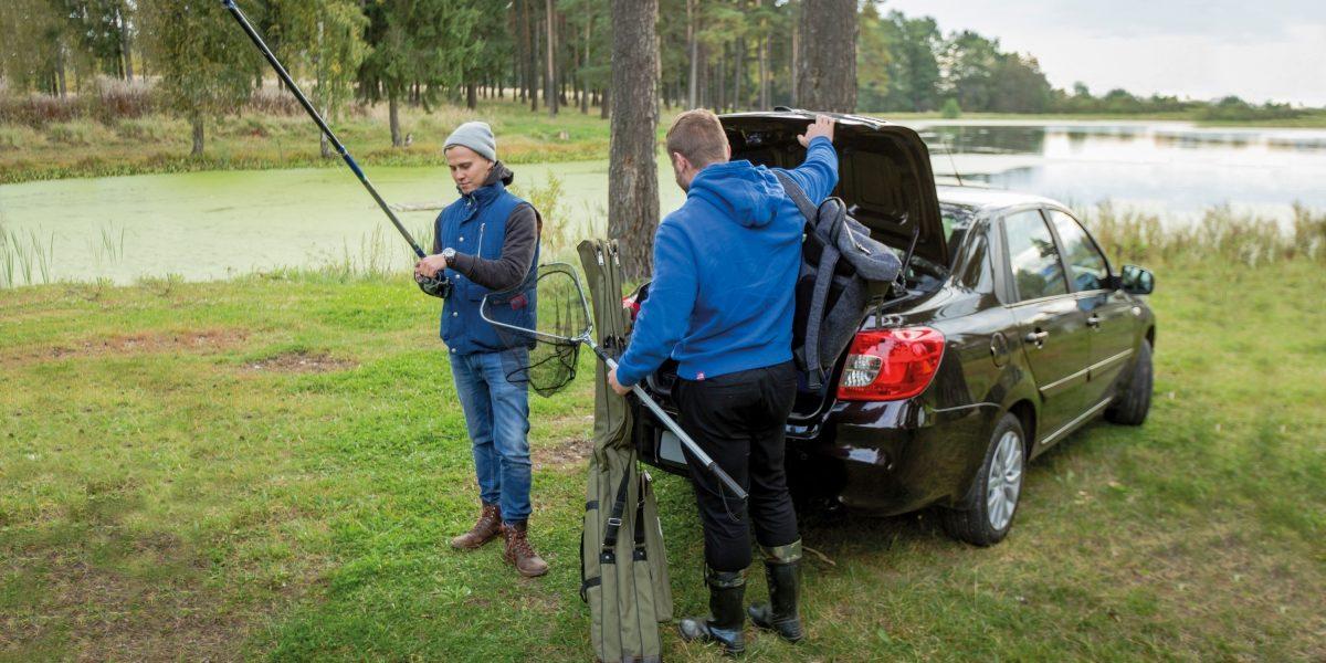 Рыболовы открывают багажник автомобиля Datsun.