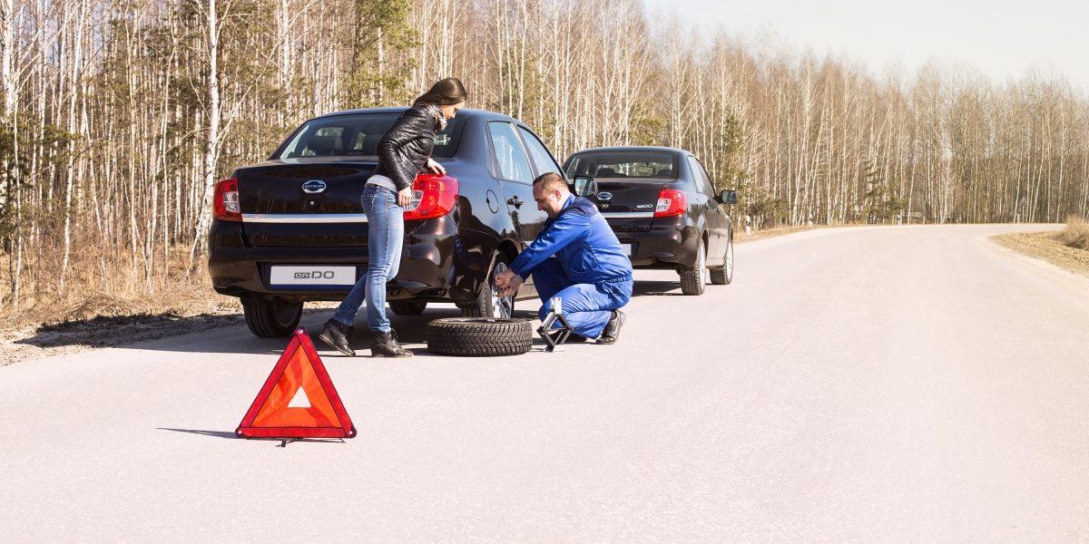 Специалист сервиса «Помощь на дорогах» Datsun меняет колесо на автомобиле Datsun